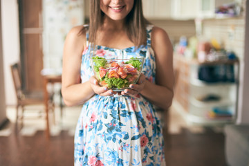 Front view of happy pregnant female standing in kitchen, keeping plate with vegetables and smiling. Young woman eating healthy food while being pregnant. Concept of care and health.