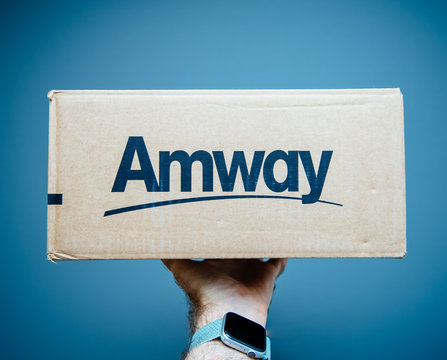Paris, France - Jul 2, 2019: Man hand holding against gray background cardboard parcel box with Amway logotype blue background