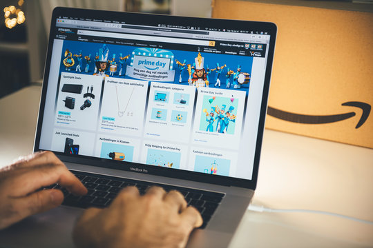 PARIS, FRANCE - JUL 16 2019: Man POV looking at Amazon Deutschland Prime Day shopping deals on Apple MacBook Pro laptop with Safari Internet website open special discounts