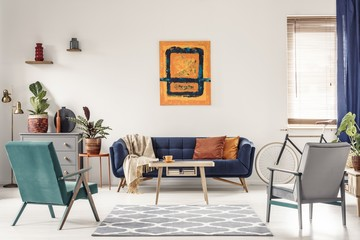 Real photo of a navy blue sofa with orange cushions and an artwo Fototapete