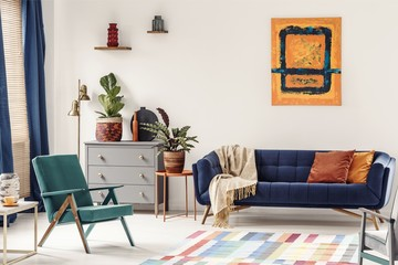 Orange end table with fresh plant standing next to navy couch wi