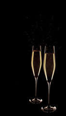 Two glasses of champagne isolated on black background