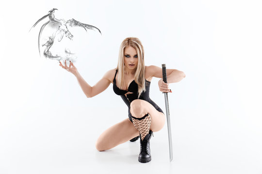 Portrait of a young woman in black clothes .The girl with the sword. Ninja girl with a katana. Photo shoot in the Studio. White background. Japanese theme