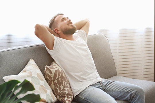 Bearded guy wearing blank white t-shirt & denim pants sitting alone at home on grey textile couch. Young man w/ facial hair in domestic situations. Interior background, copy space, close up, monstera.