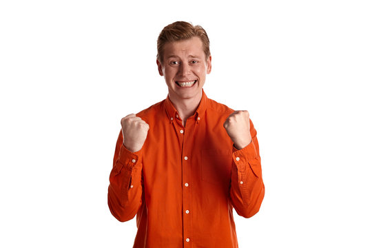 Close-up portrait of a ginger guy in orange shirt posing isolated on white background. Sincere emotions.