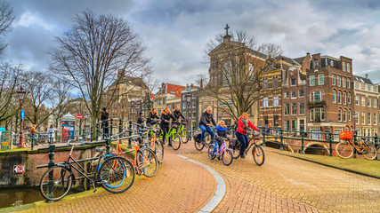 Cityscape on a sunny winter day - view on the group of cyclists in the historic center of Amsterdam, The Netherlands Fototapete