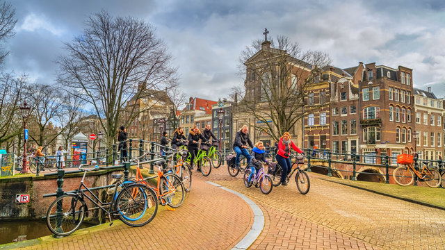 Cityscape on a sunny winter day - view on the group of cyclists in the historic center of Amsterdam, The Netherlands