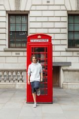 Boy stands by a telephone box