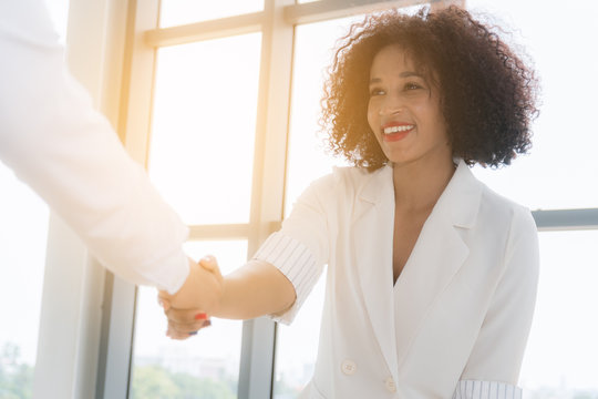 African American lady business woman shaking hand as they close a deal or partnership focus to smiling on sunlight background at office.