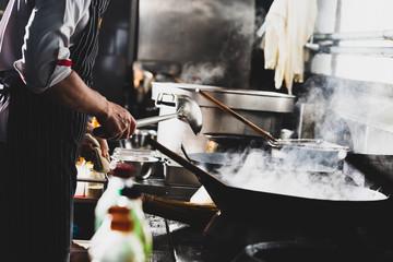 Chef stir fry in wok Wall mural