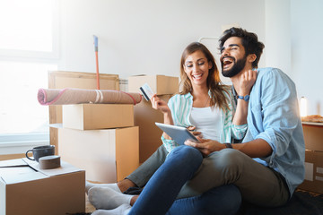 Happy young couple in love shopping online in new family home. Consumerism, love, dating, credit card, lifestyle concept  - Stock Image