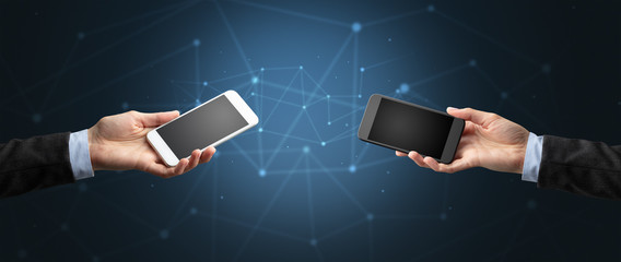 Close up of two hands holding smartphones to each other, wireless connection concept