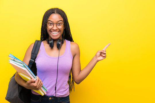 African American teenager student girl with long braided hair over isolated yellow wall pointing finger to the side