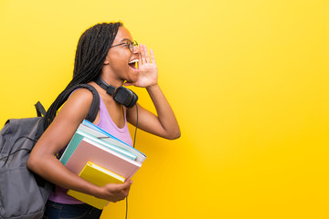 African American teenager student girl with long braided hair over isolated yellow wall shouting...