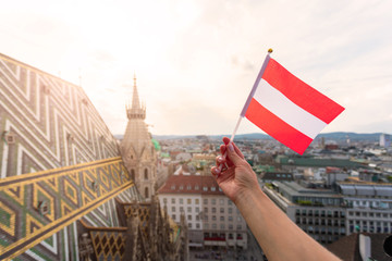 Woman holds Austria flag in hand against Vienna city panorama background.