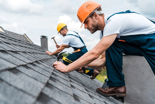 selective focus of handsome handyman repairing roof with coworker