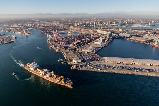 Afternoon aerial view of busy container cargo facilities and passing ship on August 16, 2016 in Long Beach, California, USA.