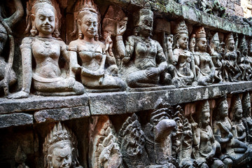 Siem Reap, Cambodia. Stone reliefs depicting a Devata and Aspara, female spirits and guardians of Hindu and Buddhist mythology on the walls along the Terrace of the Leper King