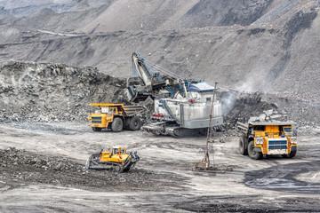 A powerful excavator loads mining trucks.