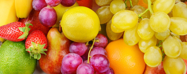 Bright beautiful background of ripe fruits. Healthy food. Wide photo. Wall mural
