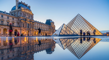 View of famous Louvre Museum with Louvre Pyramid at evening at sunset in Paris France