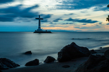 Dramatic Sunset Sky Behind a Large Cross Marking a Sunken Cemetery on Camiguin Island, Philippines