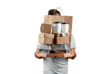 Man in a bright T-shirt giving a fast food order isolated on a white background. Male courier worker is holding food. Home delivery of goods from a store or restaurant. Copy space