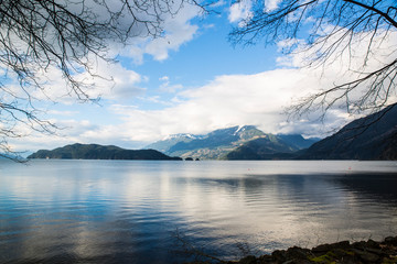 Harrison Hot Springs, British Columbia, Canada, Tree branches frame natures picture of a lake, snow and mountains Wall mural