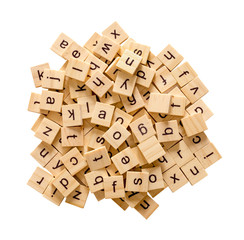 Pile of alphabet letters on wooden scrabble pieces, isolated on white background with clipping path.
