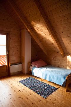 Villach, Carinthia, Austria - Interior of an attic bedroom in a rustic cabin.