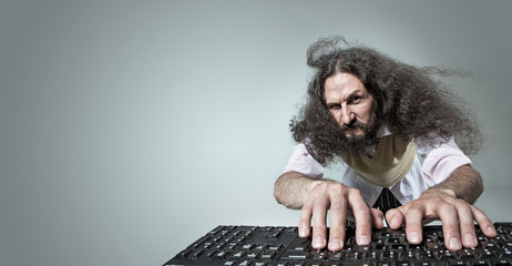 Funny portrait of a skinny nerd working with a computer
