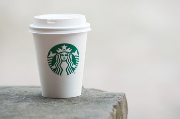 Closeup of white take away cup in outdoor from Starbuck brand, Starbuck is the famous chain of fast food
