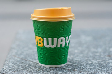 closeup of paper cup of coffee for take away from subway brand abandonned in the street - subway is the american famous brand of fast food since 1965