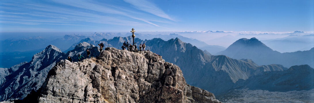 Germany, Bavaria, Zugspitze. Hikers enjoy an inspiring view to the Tirol from the Zugspitze summit in Bavaria, Germany.