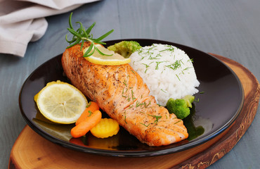 Grilled salmon fillet with rice and vegetables on black plate over wooden table