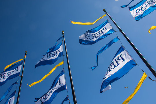 JULY 6 2017 - SAN FRANCISCO, CALIFORNIA: Flags celebrating Pier 39's 39th anniversary fly against a blue sky.
