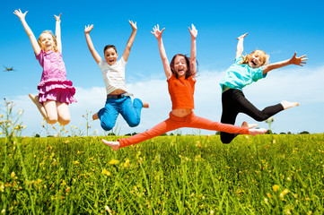 Happy active children jumping outdoors