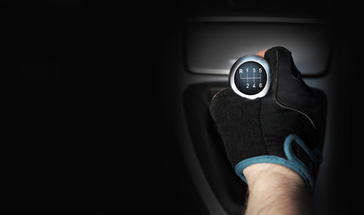 Dłoń w rękawiczce na sześcio biegowej dźwigni zmiany biegów w samochodzie osobowym, tekst.