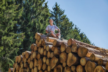 A man is sitting on a huge pile of wood.
