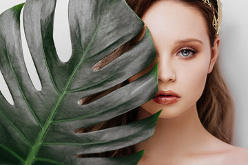 Portrait of young and beautiful woman with perfect smooth skin in tropical leaves. Wall mural