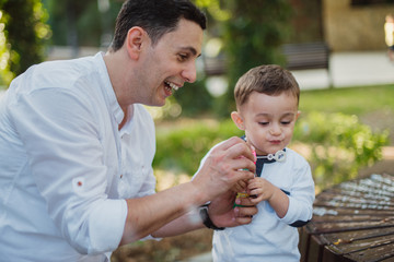 Little baby boy puff up soap bubbles with his father in the garden. Family portret concept.