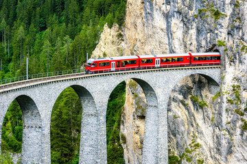 Landwasser Viaduct in Filisur, Switzerland. It is a famous landmark of Swiss Alps. Red express train runs from mountain tunnel on high bridge. Scenic aerial view of amazing railway in summer.  Wall mural