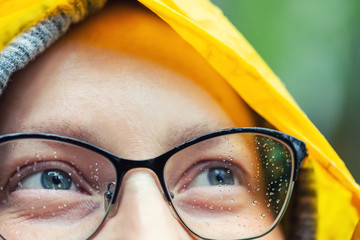 Close-up young tired happy woman portrait wearing glasses with raindrops and bright yellow raincoat hood during rain outdoors