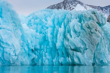 Greenland. East Greenland. Liverpool Land. Warming Island. Blue iceberg showing melting pattern.