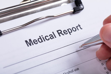 Close-up Of Human Hand Holding Pen Over Medical Report