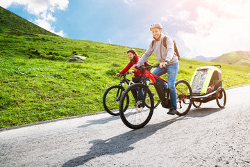 Family With Child In Trailer Riding Mountain Bikes Wall mural