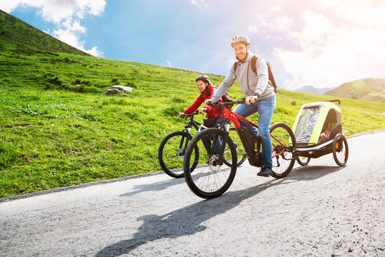 Family With Child In Trailer Riding Mountain Bikes