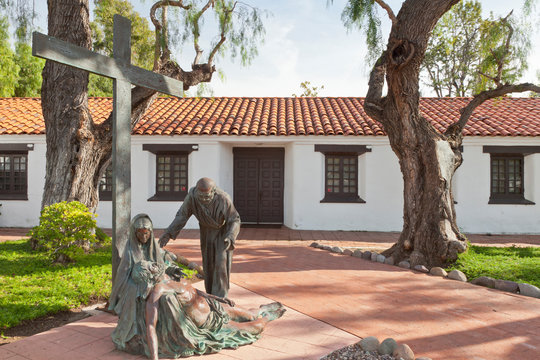 USA, California, San Diego. Religious statues and cross outside historic Mission San Diego de Alcala. Credit as: Don Paulson / Jaynes Gallery / DanitaDelimont.com