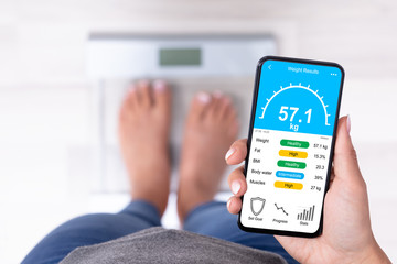 Woman Standing On Weighing Scale Holding Smartphone