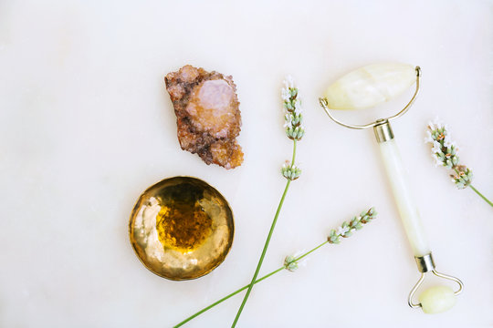 Facial oil serum in gold dish, jade roller, crystal, and floral still life on marble background